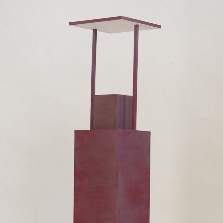 Marked by an architectural profile, this light sculpture is defined by an imposing vertical base topped with a small square and connected to the flat top light source by two slender arms. This Minimalist Silhouette evokes that of skyscrapers
