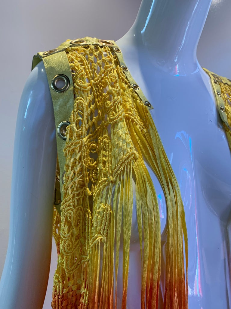 A beautiful, vibrant Torso Creations ombre-dyed rayon ribbon macrame fringe vest with yellow leather trim punctuated with eyelets in colors ranging from canary yellow to a bright reddish-orange.  Can tie at front.