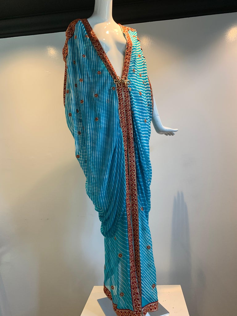 A stunning Torso Creations caftan made from exquisite vintage silk sari cloth of tie-dyed turquoise with rust and metallic thread embroidered stars and edging. Dolman effect draped sleeves and a back center adjustable drawstring for ease of