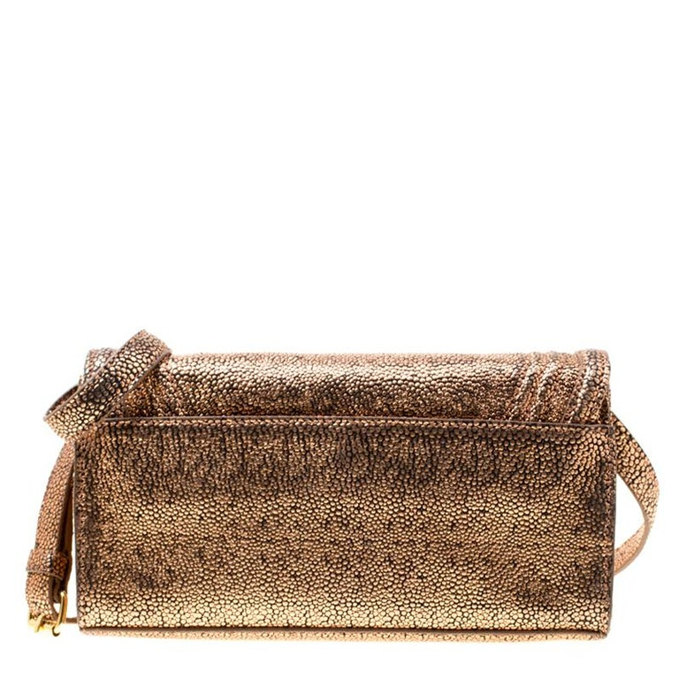 Astoundingly beautiful is this lovely clutch from Tory Burch. Crafted from textured leather in a rose gold hue it features a front flap that opens to a fabric lined interior. The bag flaunts gold-tone hardware and an adjustable shoulder