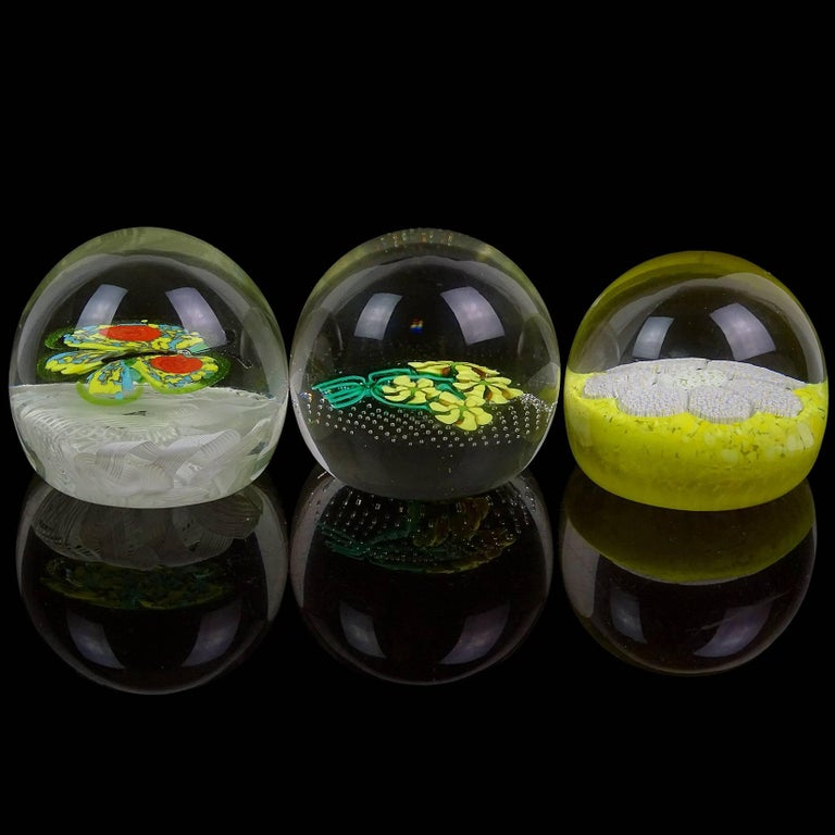 Sold individually - Beautiful set of Murano handblown flower design Italian art glass paper weights. Documented to the Fratelli Toso company. Tone paper weight has a bouquet of yellow flowers, floating on controlled bubbles. Another is filled with
