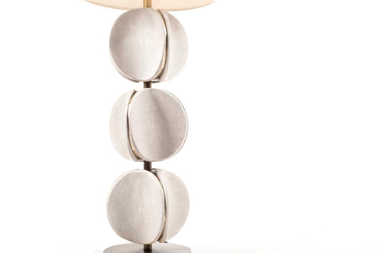 The TOTEM Lamp in cream shagreen is a playful piece with it's rotating parts. These modern TOTEM-inspired parts that concave, have subtle bronze-patina brass details that frame each part. This piece makes for a chic table table. This piece is