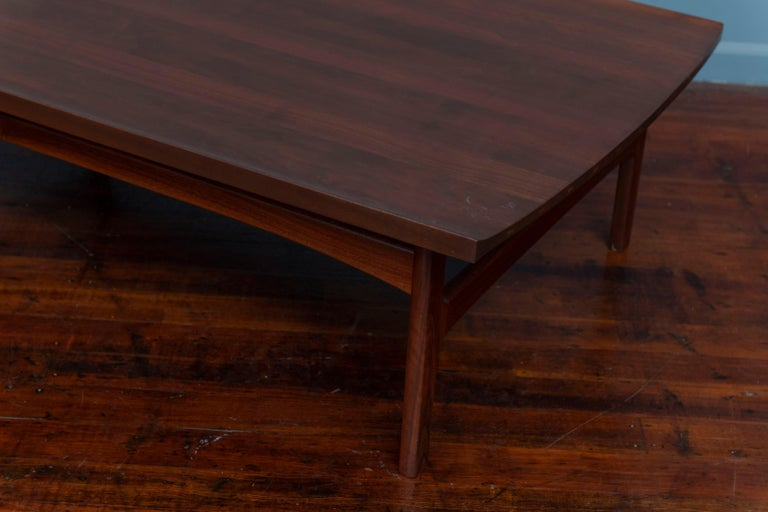 Stunning detailed solid teak Swedish coffee table featuring sculptural lipped edge top with two elegantly curved sides. Exposed wood joinery on the curved edges feature distinctive inlays in lighter, contrasting wood.  Newly refinished in a dark