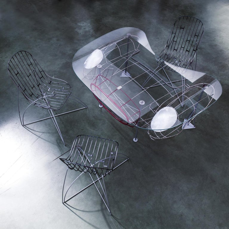 This striking design part of the Brandoli Artwork collection is the result of one of Roberto Brandoli's first and most visionary ideas. The wide glass top with beveled edges is sustained by a dramatic composition of thin iron tubes recalling the