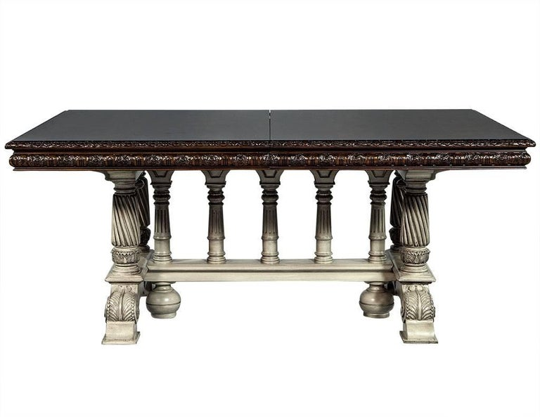 This Tudor style dining table is composed of mahogany solids and veneers with a flamed top and hand carved flowered edge. The pedestals are also hand carved and finished in a cream color. In excellent restored condition this table is perfect for a