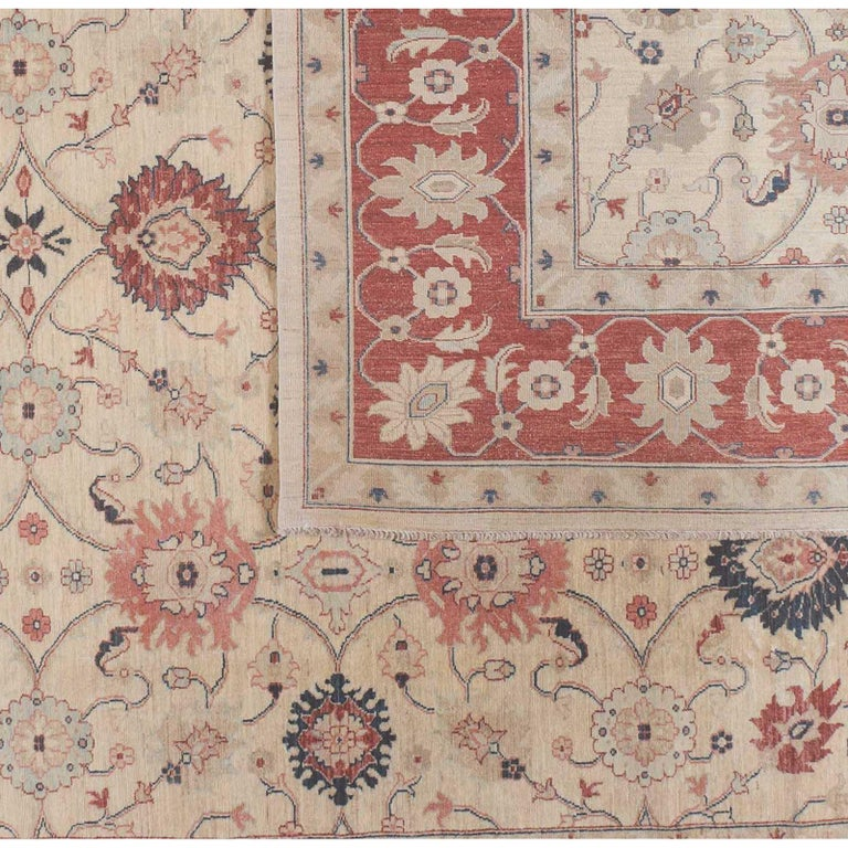 A bold red border surrounds a beige floral center in this traditional Pakistani design. Red, coral, teal and taupe flowers delight without distracting in a piece with lovely balance and proportion. Wool. Hand knotted in Pakistan using vegetal dyes.