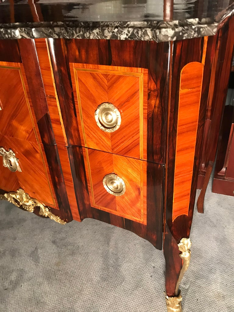 Exquisite transition commode, France 1770, rosewood and king wood veneer with delicate green colored wood inlays framing the rosewood parts. Original brass and bronze fittings and marble top. The commode has been professionally refinished and French