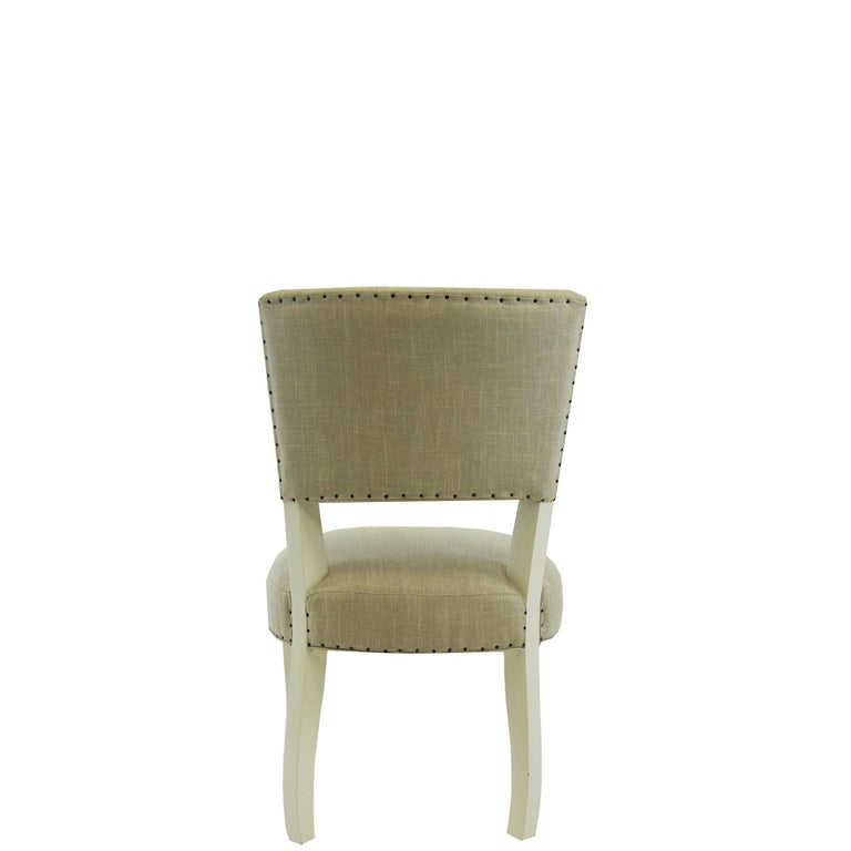 This transitional armless dining chair features a toned down cabriole leg. Comes standard with smoke colored linen and antiqued grey finish. This built to order chair is completely customizable in any finish and fabric*. This piece is handmade from