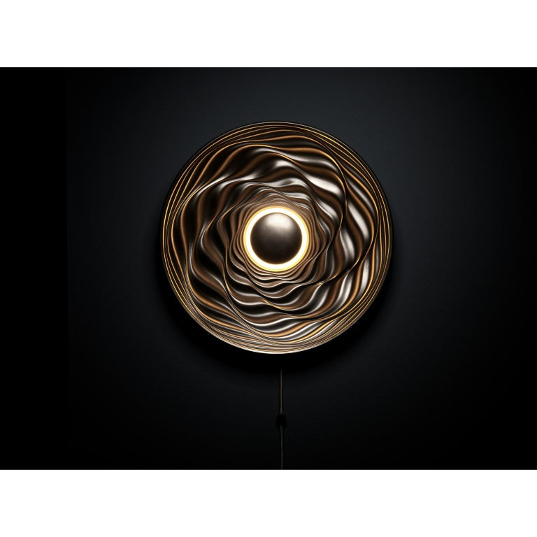 Transmission bronze sculpture by David Tragen  Dimensions: W 42.5 x D 42.5 x H 8 cm Materials: Coldcast bronze  Transmission is an illuminated wall mounted sculpture which creates different effects depending on the use of its integral