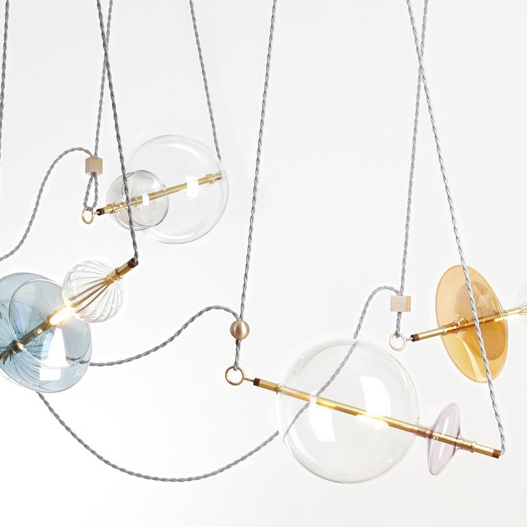 The Trapezi is a stunning contemporary chandelier inspired by a circus trapeze act and finished and assembled in Italy. The spectacular lighting fixture combines handblown glass, transparent or hand-painted A Lustro which mixes color with gold
