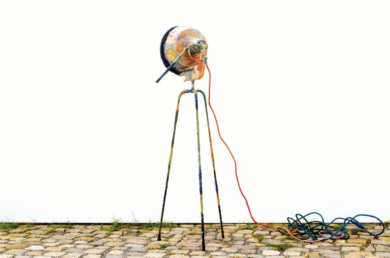 This three-legged floor lamp is covered in fabric waste that merged into a new skin. The lamp has a fine blend of colors and a rough appearance. The lamp is fully adjustable A black screen dims the light.