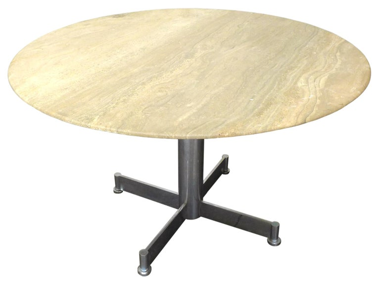 A handsome, round dining table in travertine and chromed steel.
