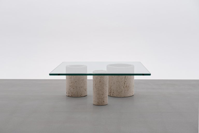Travertine coffee table by Massimo Vignelli for Casigliani, Italy 1970s. Composed of three refined travertine columns of whom each vary in diameter and a 19 mm thick glass top. The surface of the columns have a rough cylindrical line structure,