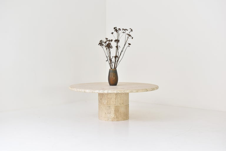 Coffee table for Up & Up, Italy 1970's. The table is fully made out of travertine with variegated tones of beige and brown. The top rests on a unique cylinder shaped pedestal base. The table is in a beautiful and original condition.