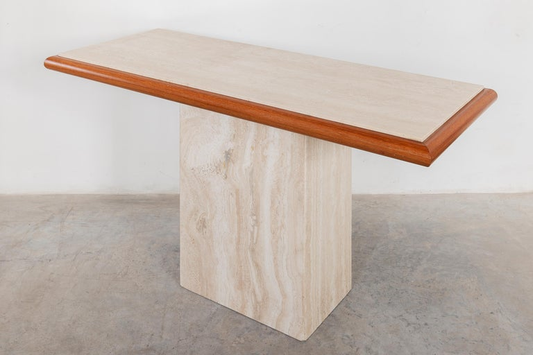 Italian Travertine 1970s console table designed by Stone International, Italy. Warm cream and gray stone table top edged in teak.  Dimensions:139W x 74H x 57D.Perfect Original Condition.