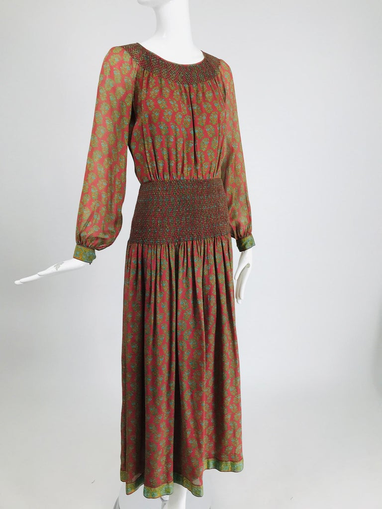 Treacy Lowe London rare hand smocked, silk print maxi dress from the 1970s. Beautiful russet silk with a green floral block print, the dress is trimmed in an arts and crafts design print. The top has long raglan sleeves with button cuffs, the neck