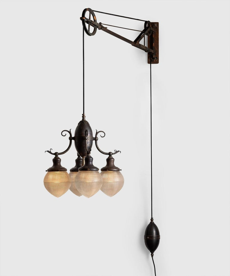Trenaman swing arm pulley lamp, America circa 1912.  Rare iron dentist lamp with four matching acorn Holophane globes, wooden backplate, and ornate details. Manufactured by Trenaman Dental MFG. CO. in New York.