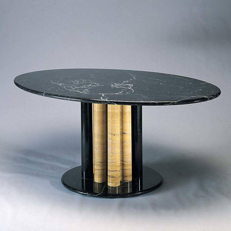 Italian design and traditional craftsmanship are harmoniously combined in this exquisite table designed by Sergio Asti in 2004 for Upgroup. The majestic oval top and the base are made of black Marquinia marble with six supporting columns, three of