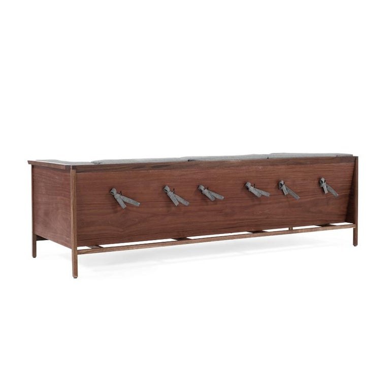 Designed exclusively for resting. Its wooden structure works as a container for a soft set of cushions. Produced in three different types of wood, tzalam, walnut and oak. One of the main distinctions of its upholstery is the use of knots on the back