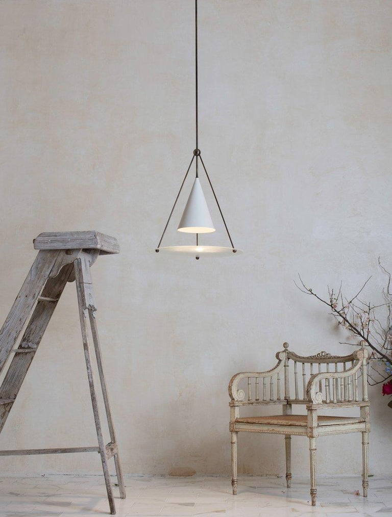 The tri cone pendant echoes it's form in 3 geometric elements. A tetrahedron structure suspends a glass disc under a cone shade that houses a focused spot-light. The light is diffused by a micro-pyramid texture in the glass resulting in a beautiful