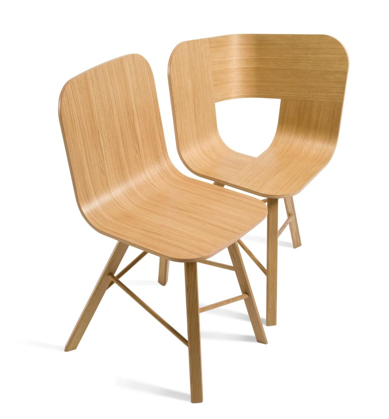 Essential and elegant chair with a bent plywood shell, and four iconic legs with triangular shape in solid oak, joined by transversal wooden bars.