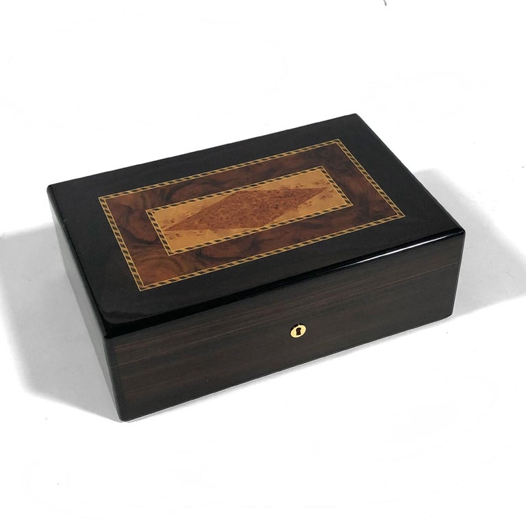 This handsome mahogany humidor made in France by Triade has a beautiful marquetry top made of a variety of woods including highly figured burl.