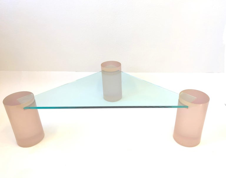 """Glamorous 1980s triangular blush pink satin Lucite and glass cocktail table in the style of Karl Springer. The table is constructed of three solid satin Lucite 8.75"""" diameter cylinders and 3/4"""" thick glass top. The glass slides in to each leg. New"""