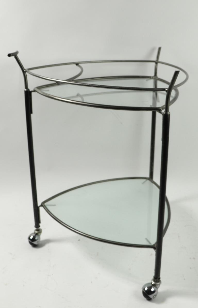 Two-tier bar or serving cart, having two glass shelves, one frosted, one clear, and a iron frame.