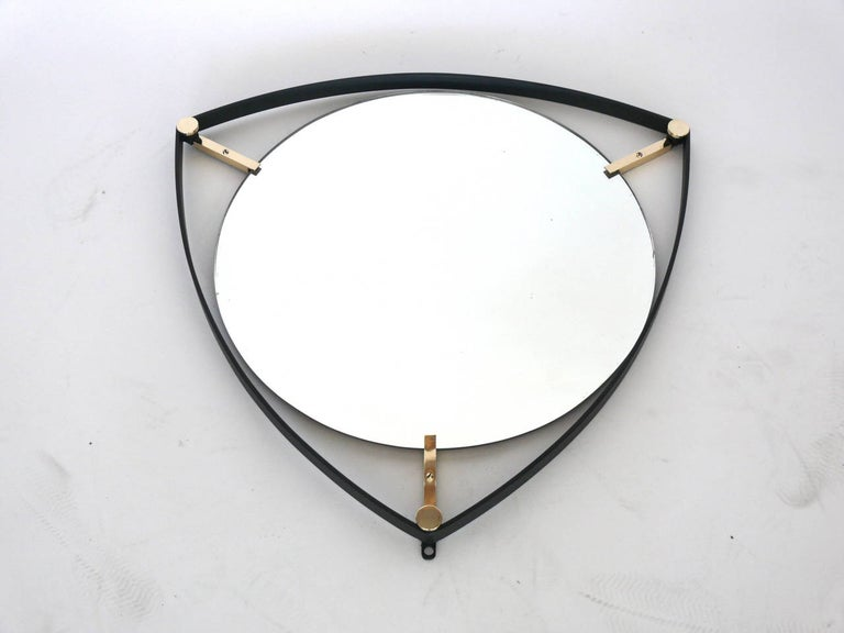 Newly produced Triangular mirror of an Italian design with circular glass floats within an iron frame, suspended by three brass tabs.