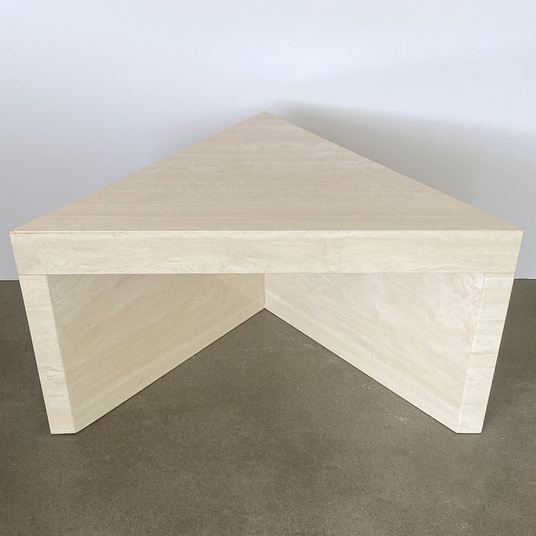 Italian solid travertine triangular shaped end table or side table, circa 1970s. This table features solid filled travertine stone with a polished finish. The stone is a pale cream color with subtle veining. The two legs are 1.75