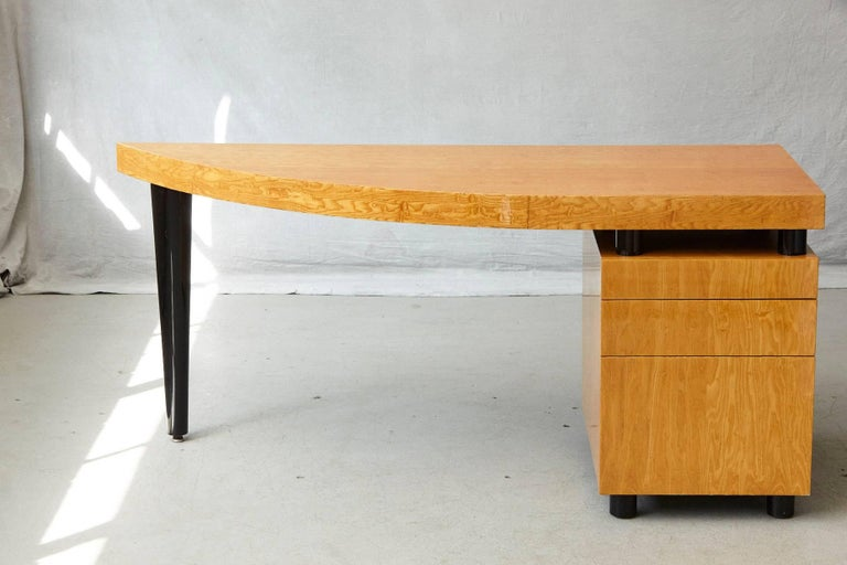 Triangular, almost sail-shaped desk in high gloss lacquered walnut with three drawers. The desk is mounted on cylindrical black lacquered legs, with one prominent tapered black lacquered leg.