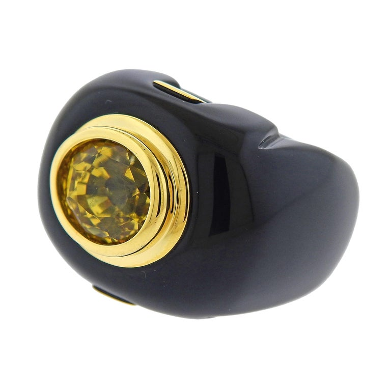 18k yellow gold and onyx ring by Trianon / Seaman Schepps , set with an oval 10.50ct yellow sapphire center stone. Ring size 5.75, ring top is 20mm wide, weighs 16.5 grams. Marked: 750, Trianon mark, 44735.