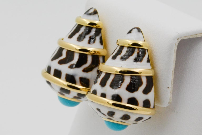 From Trianon, these 18k yellow gold Conus Ebraus earrings are in a shell design with three yellow gold bands and cabochon turquoise accents with clip backs. Signed Trianon.