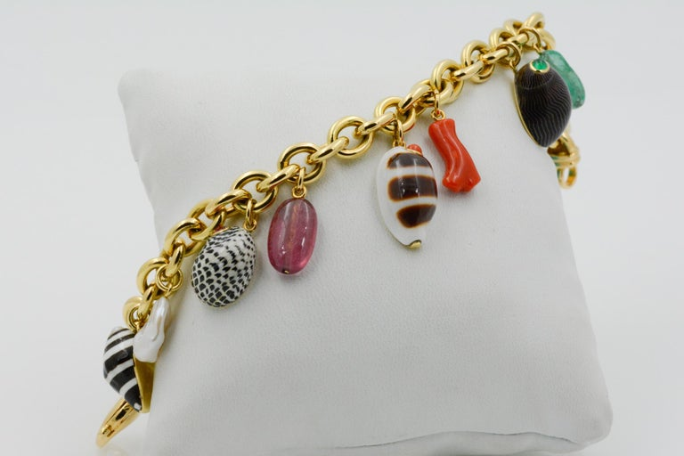 From Tiranon, this 18 karat yellow gold charm bracelet features five different shell charms with center stones and five nugget stone charms set in 18 karat yellow gold. Signed Trianon