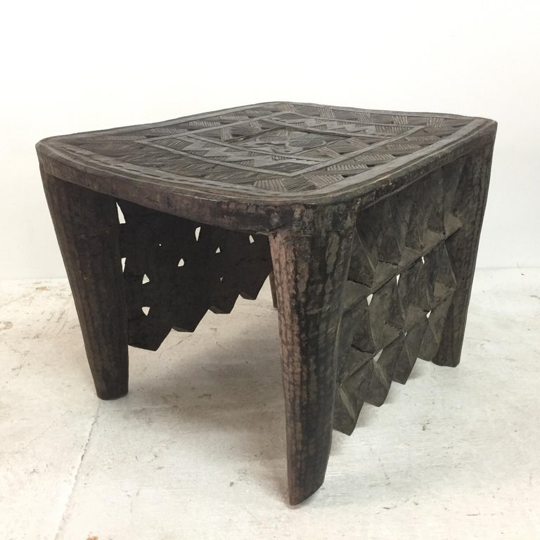This beautifully carved African tribal table has two lateral sides fully carved to floor and two open sides (see detail images). The center top has a hidden compartment. Great as a bench or side table!
