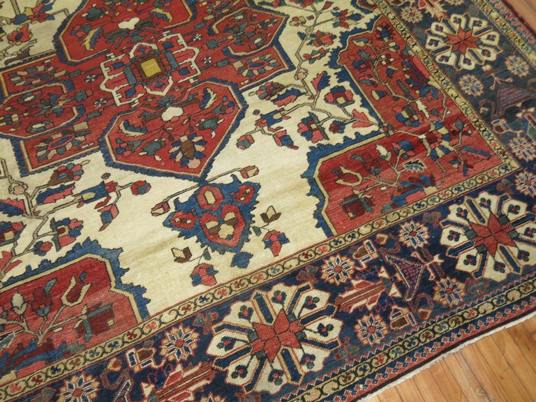 An antique Persian Bakhtiari rug with large scale all-over tribal medallion design on an antique white background.