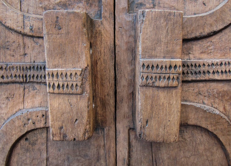This exceptional piece is one of the few impressively carved granary doors which have survived to our days. Created in the village of Wakching, in the Indian state of Nagaland, it evinces two central cylinders at each wing through which two tapering
