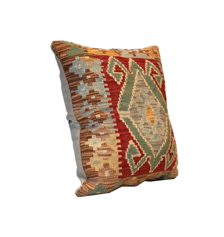 This traditional Kilim cushion cover has been handwoven with the traditional Kilim, flat-weave technique. Featuring a geometric pattern woven in beige, red, blue, green and mustard. 