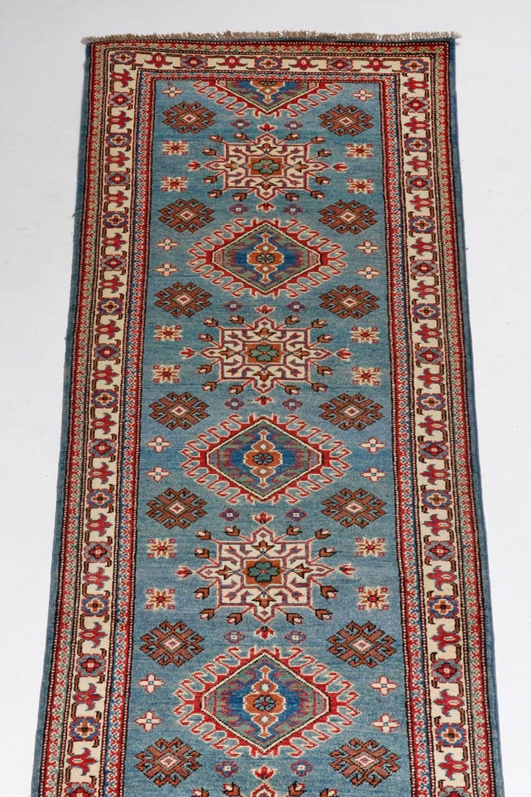 Dramatic Pakistani Runner Rug made in a Kazak style. Features a field of bold sky blue covered in geometric shapes. Multiple borders frame the field and the condition is excellent.
