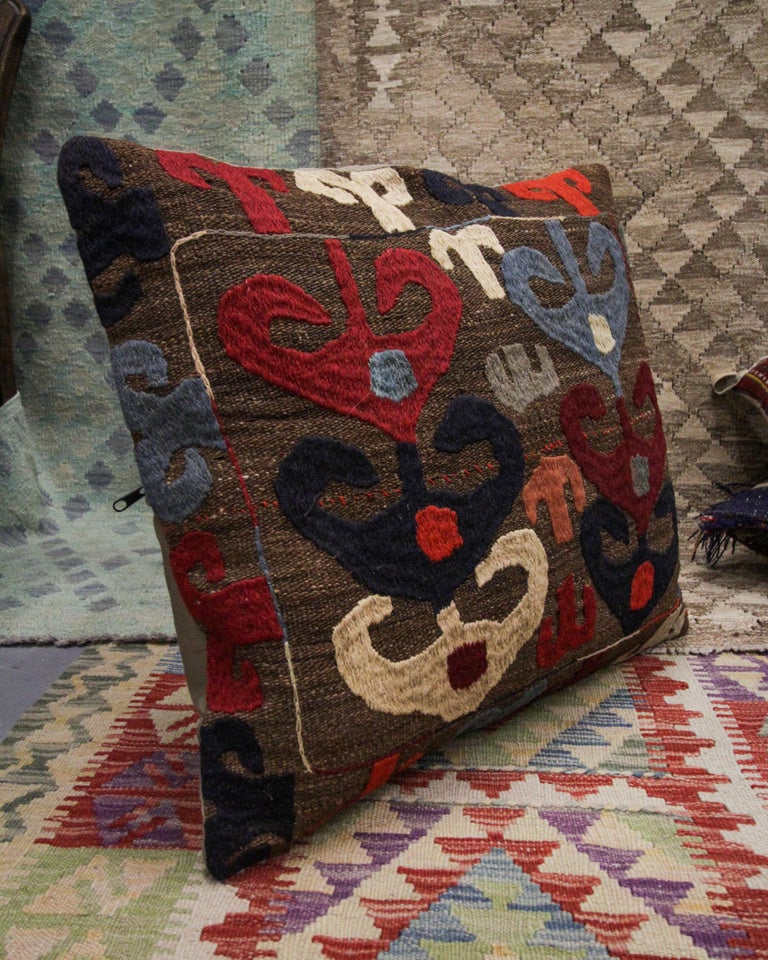 This truly unique tribal cushion cover is a larger piece suited to a bed or a sofa. Woven with a one of a kind repeating tribal motif pattern in accents of brown, beige, red and deep blue on a beige-brown background. This cushion's colour palette