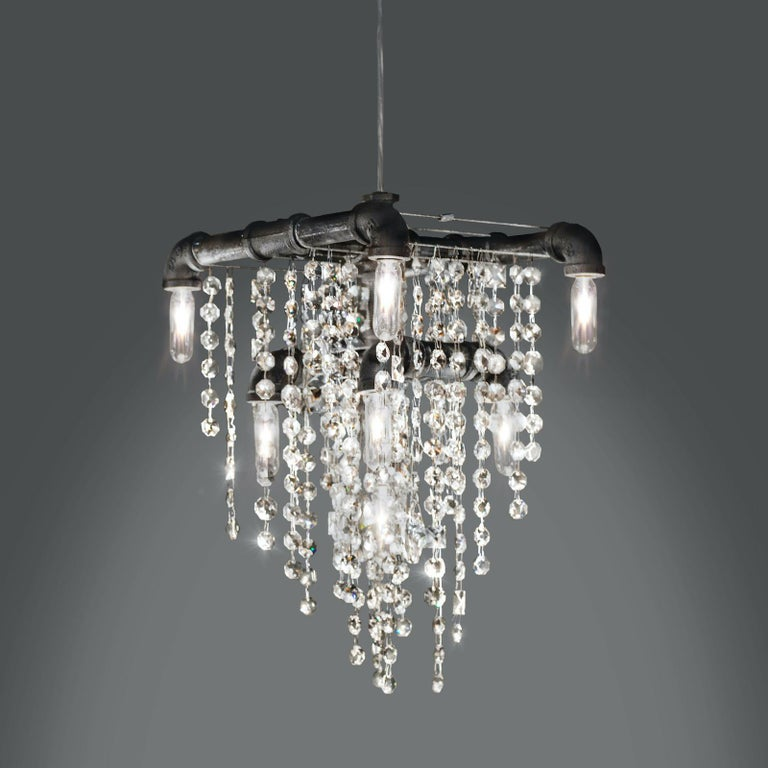 At first glance, the 9-bulb Tribeca chandelier pendant looks like a traditional tiered chandelier. But wait, something is different... The structure of this chandelier is formed by black steel gas pipes and fittings to create a masculine frame. That