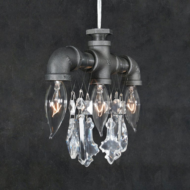This three-bulb Tribeca chandelier pendant is an Industrial-chic light comprised of rough black steel pipes and fittings, contrasted with high-quality gem-cut crystal. Often used to light up areas where a single source of light just won't do. This