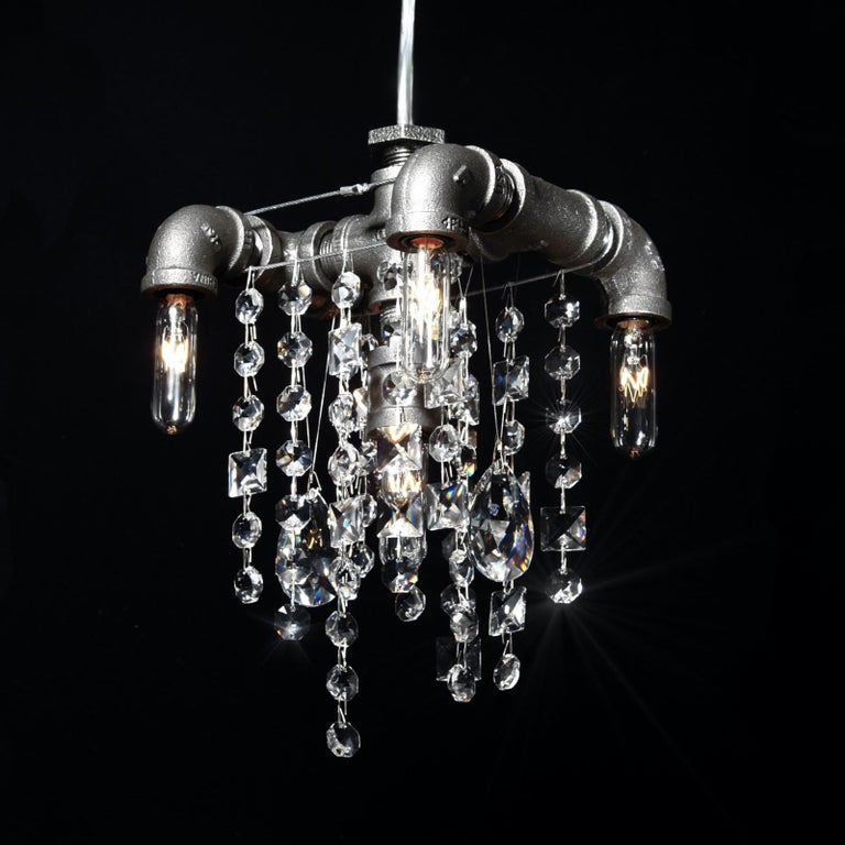 The 5-bulb Tribeca compact chandelier pendant features a compact Industrial frame of sturdy black steel gas pipes and fittings. With five lights cascading over two levels, paired with superior quality and optically-pure gem-cut crystal in a random