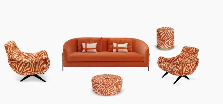 The armchair is offered in the version made of linen with wild animal pattern in the orange and cream colors, is inspired by the 1950s design and interpreted again with soft padding and its sartorial details. The thin and crossed metal legs give the