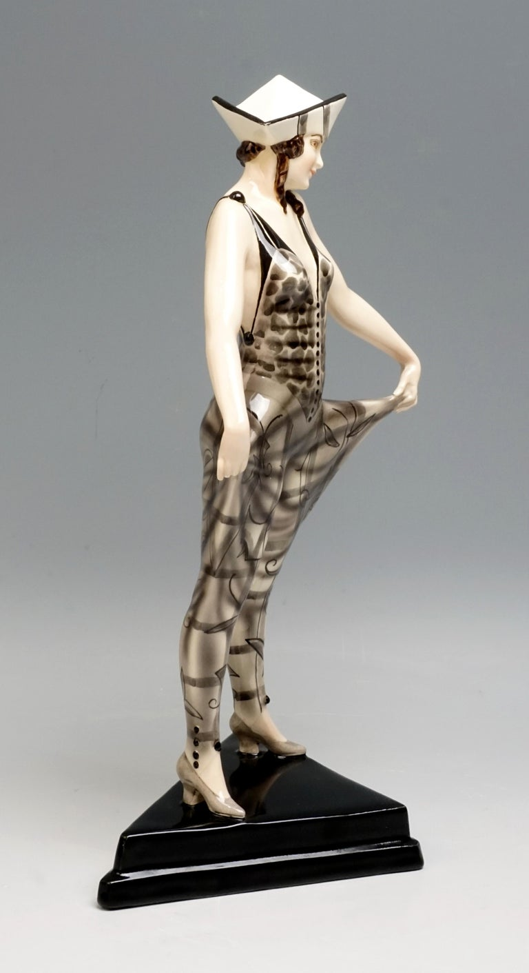 Very rare Art Deco goldscheider ceramics figurine, circa 1930  The young lady is wearing a carnival costume and a tricorn hat. The triangular straps of her bodice are connected at the top by large buttons, with the legs wide apart and the pulling