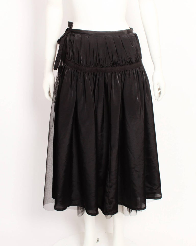 Tricot by Comme Des Garcons black tulle wrap skirt features a net skirt and solid underskirt that zip together. The silhouette is full and gathered with strips of of cotton tape that run around the waist and hipline. These hold the gathers in place