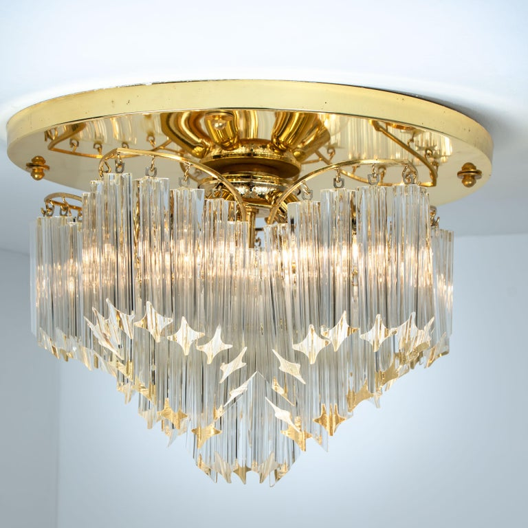 This exceptional flush mount was manufactured by Venini in Italy. The lamp has clear Murano Triedri crystals of varying lengths that create a great light effect. The crystals are suspended on beautifully constructed gold-plated frame.  This Venini