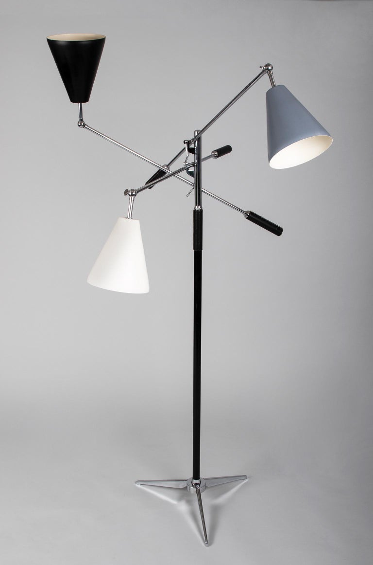 Italy, 1950s   An architectural triennale floor lamp in the style of Angelo Lelii (sometimes spelled Angelo Lelli) for Arredoluce, with three moveable cone-shaped shades enameled in white, grey, and black. Supported by a partially leather-clad shaft