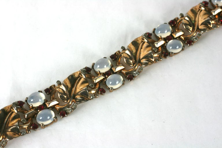Trifari,  Alfred Philippe Retro sterling vermeil golden leaf link bracelet of faux moonstone cabochons and ruby crystals. Each leaf panel is further accented in minute crystal pave rhinestones. Marked: Trifari with Crown Des Pat No 140780,