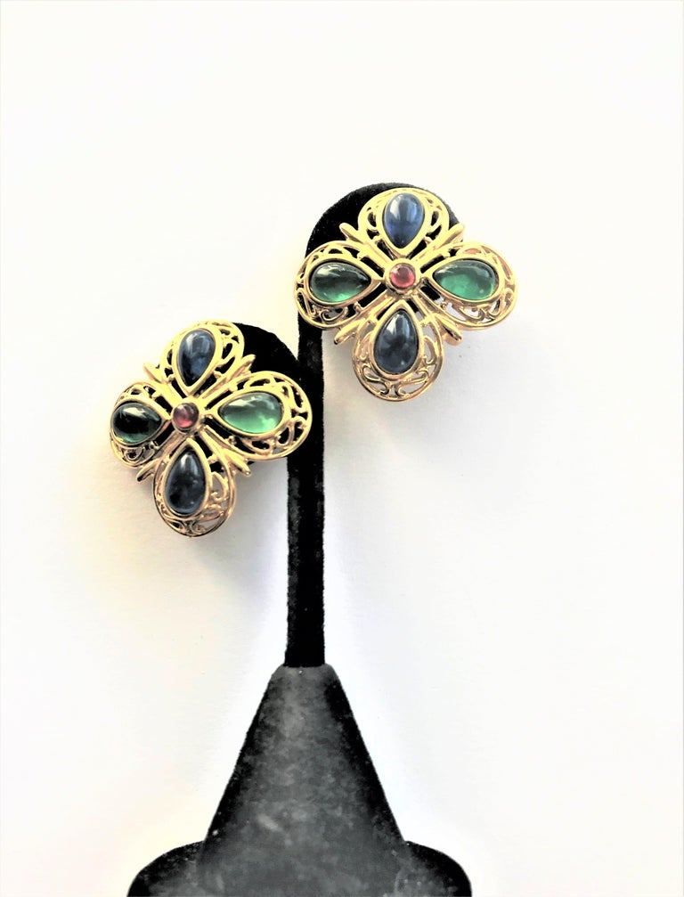 Trifari ear clips in the shape of 2 4-leaf clover with blue and green  glass drops. Edged with openwork gold work. In the middle a small red glas stone. On the back of the clips bracket Trifari signature.  Measurement:  3.5 x 3.5 cm - easy to wear -